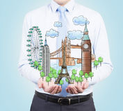A person in formal clothes holds in his hands a sketch of famous places from all over the world. Stock Photography