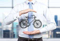 A person in formal clothes holds a sketched bicycle between his hands.  Royalty Free Stock Image