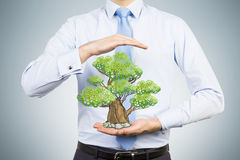 A person in formal clothes holds a sketched tree between his hands Stock Photos
