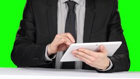 Person in formal suit sitting at the table and uses laptop. Green screen stock footage