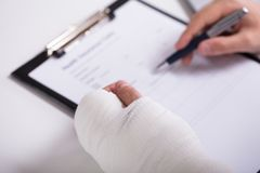 Person With Fractured Hand Filling Health Insurance Form royalty free stock images