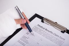 Person With Fractured Hand Filling Medical Benefit Claim Form royalty free stock photography