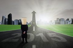 Person on the future road of 2015. Businessman in formal suit with cardboard head standing on the highway turning into arrow upward toward the future of 2015 Stock Image