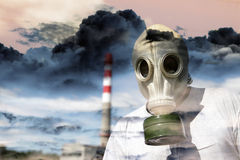 Person in a gas mask. Against a pipe polluting air Stock Image