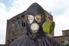 Person in gas mask against the backdrop of abandoned building Royalty Free Stock Photography