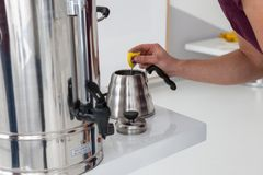 Man pours water. A person gently pours hot water into a metal kettle Stock Images
