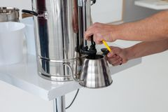 Man pours water. A person gently pours hot water into a metal kettle Royalty Free Stock Images