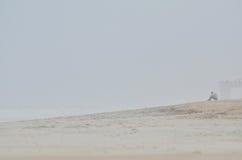 Person gesessen auf nebelhaftem Strand Lizenzfreies Stockfoto