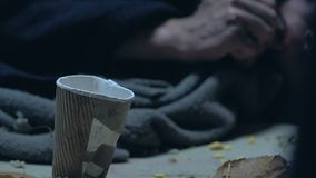 Person gives money to homeless man eating bread, worldwide hunger and poverty