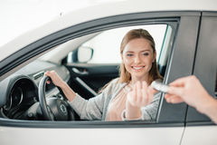 Person giving car key to woman sitting in car Royalty Free Stock Photo