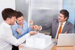 Person Giving Keys To Man Lizenzfreie Stockfotos