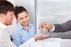 Person giving keys to man Stock Photo