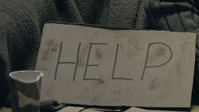 Person giving money to beggar with Help sign, compassion and donations for poor. Stock footage stock footage