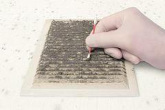 Check ventilation pollution. Person gloved check ventilation in the dirt with a cotton swab, cleaning dusty ventilation grilles, on a moldy white wall Royalty Free Stock Photos