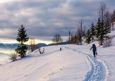 Person go through snowy rural hillside. Person go through snowy hillside. beautiful scenery of mountainous countryside in winter Stock Photos