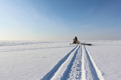 The person going on a snowmobile on the frozen river Royalty Free Stock Photo
