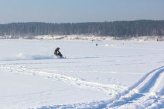The person going on a snowmobile on the frozen river Stock Images