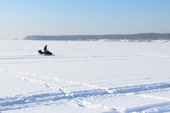 The person going on a snowmobile on the frozen river Royalty Free Stock Photography