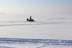 The person going on a snowmobile on the frozen river Stock Image