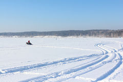 The person going on a snowmobile on the frozen river Royalty Free Stock Images