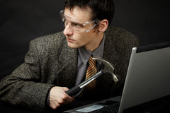 Person is going to break computer. The person is going to break the computer by means of a hammer Stock Images