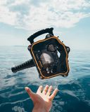 Person Grabbing Black and Orange Plastic Case Front of Calm Water Royalty Free Stock Image