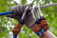 Person in Gray and Beige Gloves Holding on Gray Cable Wire Royalty Free Stock Photography