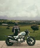 Person in Gray Hooded Jacket Leaning on White and Blue Cafe Racer With View of Green Field Under White Clouds during Daytime Stock Photography