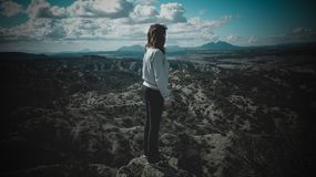 Person in Gray Long-sleeved Shirt Standing on Top of Mountain Stock Images