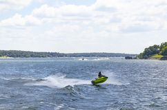 Person on a green PWC catches air on lake with other boats and PWCs and houses and docks on the shore in the background. A Person on a green PWC catches air on royalty free stock image