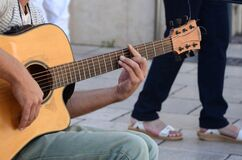 Person in Grey Shirt and Blue Denim Jeans Playing Acoustic Guitar Stock Image