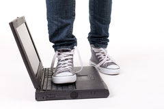 Person in gym shoes standing on laptop Stock Images