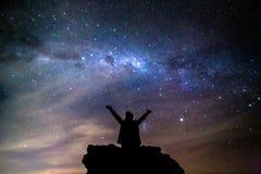 Person hagelt den Kosmos, den Milchstraße nächtlichen Himmel die Hauptrolle spielt lizenzfreie stockfotos