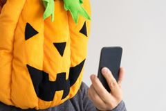 A person in the Halloween pumpkin costume taking a selfie royalty free stock image