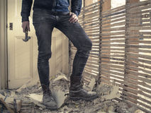 Person with hammer standing by wattle and daub wall. A person holding a hammer is standing by an old wattle and daub wall Stock Images