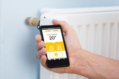 Person hand adjusting temperature of thermostat using cellphone Royalty Free Stock Image