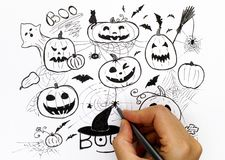 Person hand with black pen drawing Halloween picture. Royalty Free Stock Images