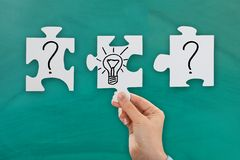 Person hand with bulb and question mark Royalty Free Stock Image