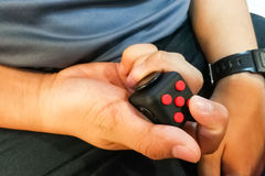 Person hand enjoy, play, relieve with the fidget cube Stock Photo