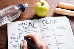 Person Hand Filling Meal Plan In Notebook. High Angle View Of A Person Hand Filling Meal Plan In Notebook At Wooden Desk Stock Image