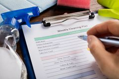 Person Hand Filling Weekly Cleaning Plan Form Stock Images