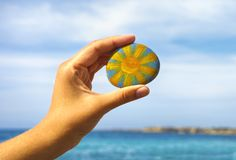 Person hand hold pebble with painted bright sun against blue sky. And sea. Close-up Stock Photography