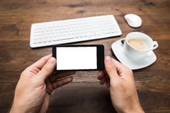 Person Hand Holding Mobile Phone At Desk Royalty Free Stock Images