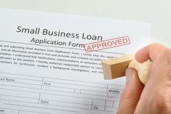 Person hand holding rubber stamp over loan application Stock Photo