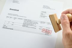 Person hand holding rubber stamp over paid invoice Stock Photos