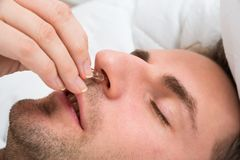 Person hand inserting nose clip device into nose Stock Images