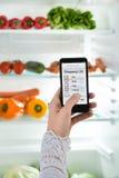 Person Hand With Mobile Phone que muestra la lista de compras Foto de archivo
