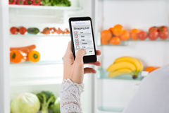 Person Hand With Mobile Phone que muestra la lista de compras Fotografía de archivo libre de regalías