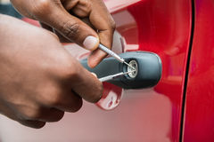 Person Hand Opening Car Door mit Lockpicker Lizenzfreies Stockfoto