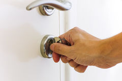 Person hand opening door by key Royalty Free Stock Photo
